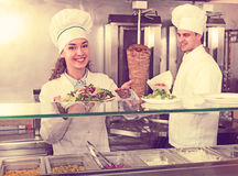 Chefs with kebab and salad at bistro Stock Photos