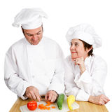 Chefs - Observing Preperation. One chef observes another's prep work, chopping vegetables. Isolated on white stock photos