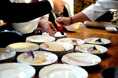 Chefs occupés dans un restaurant s'chargeant et décorant de la nourriture délicieuse fascinante sur une table en bois pour un dîn photo libre de droits