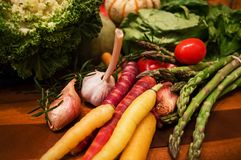 Organic healthy fall harvest vegetables. A colourful selection of nutritious fresh fall harvest vegetables in a chefs kitchen on dark wood chopping board Royalty Free Stock Photography