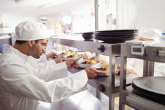 Chefs passing ready food to waiter at order station. In commercial kitchen stock photo
