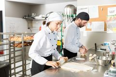 Chefs Preparing Bread Dough In Kitchen. Female chef rolling dough while working with colleague in bakery royalty free stock images