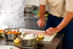 Chefs preparing fish in restaurant or hotel kitchen. Close up of chefs in a commercial restaurant or hotel kitchen working, they are preparing an fish fillet and Stock Image