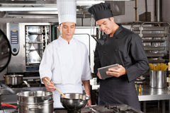 Chefs Preparing Food In Kitchen. Male chef with digital computer assisting colleague in preparing food at kitchen stock photography