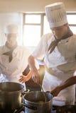 Chefs preparing food at stove Stock Photo