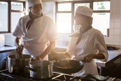 Chefs preparing food at stove Royalty Free Stock Photos