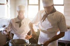 Chefs preparing food at stove Stock Image