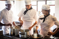 Chefs preparing food at stove. In commercial kitchen royalty free stock photography