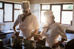 Chefs preparing food at stove Stock Photography