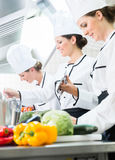 Chefs preparing meals in commercial kitchen Stock Photos