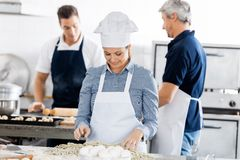 Chefs Preparing Pasta In Kitchen Stock Photo