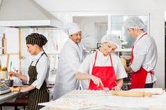 Chefs Preparing Pasta In Kitchen Stock Photos