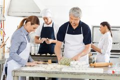 Chefs Preparing Pasta Together In Kitchen Royalty Free Stock Image