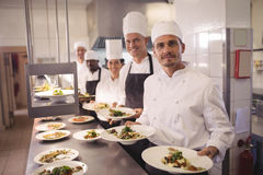 Chefs presenting food plates. Portrait of chefs presenting food plates in the commercial kitchen stock photo