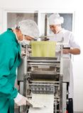 Chefs Processing Ravioli Pasta In Machine Royalty Free Stock Photos
