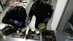 Chefs professionnels dans la cuisine de restaurant plaçant la nourriture sur trois plats noirs préparant les plats pour des clien clips vidéos