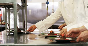 Chefs putting finishing touch on desserts stock footage