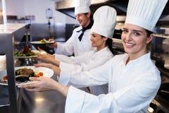 Chefs remettant des plats de dîner par la station d'ordre photographie stock