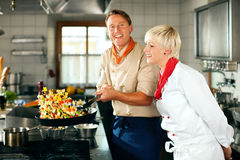 Chefs in a restaurant or hotel kitchen cooking Royalty Free Stock Photo