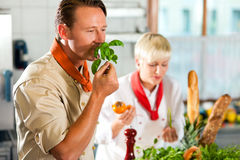 Chefs in a restaurant or hotel kitchen cooking Royalty Free Stock Images