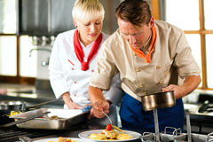 Chefs in a restaurant or hotel kitchen cooking Royalty Free Stock Image
