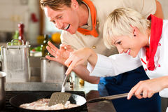 Chefs in a restaurant or hotel kitchen cooking. Two chefs in teamwork - man and woman - in a restaurant or hotel kitchen cooking delicious fish in pan royalty free stock photo