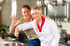 Chefs in a restaurant or hotel kitchen cooking Royalty Free Stock Photography