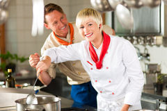 Chefs in a restaurant or hotel kitchen cooking Stock Images