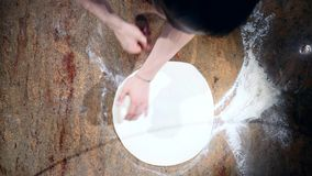 Chefs rotate pizza dough in the air. Top view stock video footage