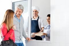 Chefs Selling Uncooked Pasta Packet To Couple Royalty Free Stock Images