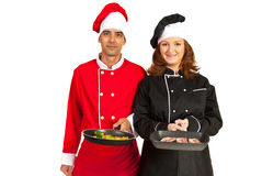 Chefs showing frying pans with food Royalty Free Stock Images