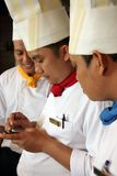Chefs smiling. Three chefs smiling at work holding PDA Royalty Free Stock Photography