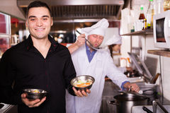 Chefs and smiling waiter working Royalty Free Stock Photos