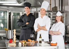 Chefs Standing With Arms Crossed. Portrait of confident chefs standing with arms crossed by kitchen counter Royalty Free Stock Images