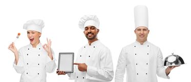 Chefs with tablet computer, cloche and tomato royalty free stock photos