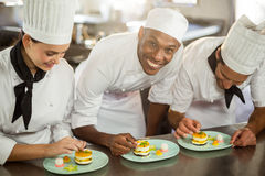 Chefs team finishing dessert plates royalty free stock photo