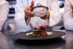 Chefs team finishing dessert plates Stock Image