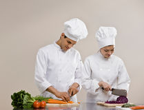Chefs in toques preparing and chopping food Royalty Free Stock Photos