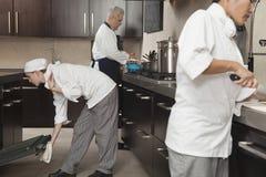 Chefs travaillant ensemble dans la cuisine commerciale Photo stock