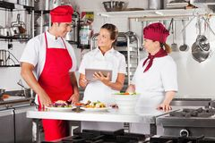 Chefs Using Tablet Computer At Kitchen Counter. Female chef with colleagues looking for recipe on a tablet computer while cooking at kitchen Royalty Free Stock Photos