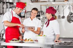 Chefs Using Tablet Computer At Kitchen Counter Stock Photography