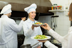 Chefs and waitress at kitchen Royalty Free Stock Photos