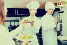 Chefs and waitress at kitchen. Team of chefs and young waitress at restaurant kitchen. Focus on girl stock photos