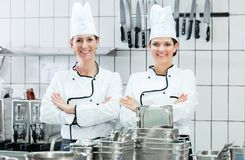 Chefs wearing working clothes in industrial kitchen Royalty Free Stock Images