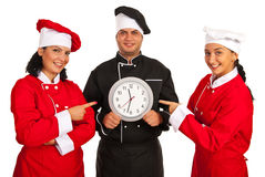 Chefs women pointing to clock. In chef men hands isolated on white background royalty free stock photos