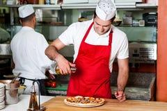 Chefs at work inside restaurant kitchen stock image