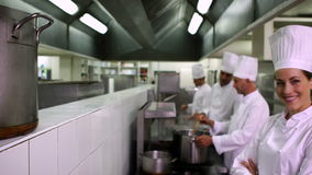 Chefs working at the stove with one smiling at camera