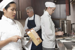 Chefs Working Together In Commercial Kitchen. Three chefs working together in busy commercial kitchen stock photography