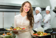 Chefs and young waiter. Team of chefs and young beautiful waiter at the restaurant kitchen stock photo