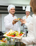 Chefs and young waiter Stock Image